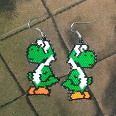 These really cute Yoshi earrings are done in brick stitch and take about 2.5 hours to make the pair. They measure about 1.5″ by 2″ in size, and are made up of 410 beads per earring. This little green dinosaur guys are so cute!  This item gives 25% of the purchase price to Kiva.org.