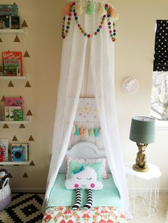 Interior design by Maya Ostrander. Toddler bed, bed canopy, felt balls, tassels, book ledges, library, kids books, roman shades, polka dots, cloud pillow, custom toddler bedding, flamingo print, bunny lamp (PB Teen), Ikea rug.