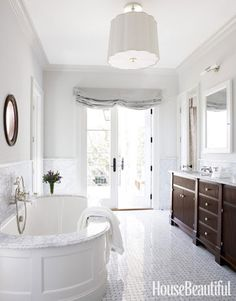 "Perfectly Polished Bathroom. The tiles in this Georgia house's bathroom shine. ""Many people use matte tiles these days, but the lustrous, spa-like finish of polished tile — it feels expensive,"" designer Jim Howard says. Waterworks Classic oval tub."
