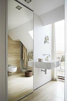 Bag den store spejlvæg i badeværelset gemmer sig et skab til opbevaring. Det er ligesom mange andre steder i lejligheden indbygget og godt gemt væk.