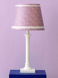 After adhering patterned paper to a lampshade, add grosgrain ribbon to the top and bottom edges. Keep the ribbon in place with small stitches or clear double-sided tape.