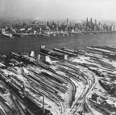 Erie and Lackawanna railroad yards and lots of trains in the snow at Hoboken, New Jersey with Lower Manhattan across the Hudson. 1950s