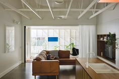The living room is contained within the original structure, its ceiling removed to expose the timber trusses.
