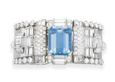 A STYLISH AQUAMARINE AND DIAMOND BRACELET, BY VAN CLEEF & ARPELS  The hinged platinum cuff, centering upon a cut-cornered rectangular-cut aquamarine, with baguette and circular-cut diamond detail, flanked on either side by circular and baguette-cut diamond openwork geometric panels, trimmed by larger circular-cut diamonds, to the polished platinum band, mounted in platinum and 18k white gold, 1955, 2 1/8 ins. diameter, in a Van Cleef & Arpels black leather case