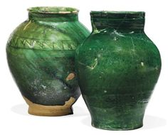 TWO FATIMID GREEN-GLAZED POTTERY JARS   EGYPT, CIRCA 11TH CENTURY   Of baluster form on short foot, one incised with a geometric band around the shoulder