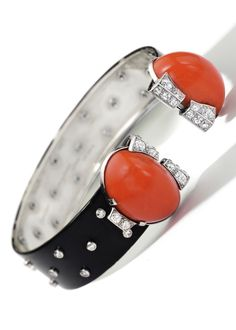 Cartier - An Art Deco Coral, Lacquer and Diamond Bangle, Circa 1930. Designed as a black lacquer band embellished with collet-set single-cut diamonds, opening to the front set with two cabochon coral with old-cut diamond details, mounted in platinum and white gold, signed Cartier, numbered, with French assay and maker's marks. #Cartier #ArtDeco