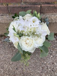 Bouquet made with all white flowers including hydrangea, rose, lisianthus, dendrobium orchids and accented with euclyptus greens.