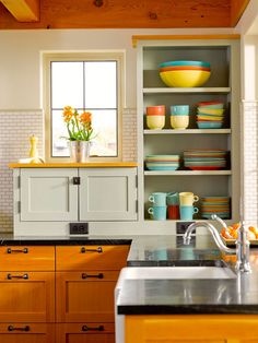 Open shelving, farm sink, soapstone counter with vibrant orange stained wood cabinets.