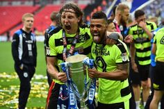 Huddersfield Town's German defender Michael Hefele (centre left) and Huddersfield Town's Bermudan striker Nahki Wells (centre right) hold the Championship Playoff trophy as Huddersfield's players celebrate winning the penalty shoot-out on the pitch after the English Championship play-off final football match between Huddersfield Town and Reading at Wembley Stadium in London on May 29, 2017..Huddersfield won the penalty shoot-out 4-3 after the game finished 0-0 after extra time. / AFP PHOTO…