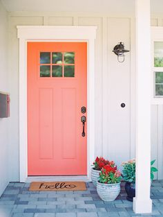 coral front door on a gray house