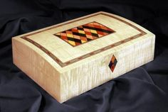 "A domed top jewellery box veneered with figured maple, 10"" x 8"" x 4"" decorated in dyed veneers. The escutcheon is formed from four harlequins - I often do this design with the keyhole cut into the top harlequin. However, for the purposes of balance as this box was relatively low, the escutcheon actually overlaps the lid margin and it made sense on this occasion for the keyhole to be in the bottom one. French polished."