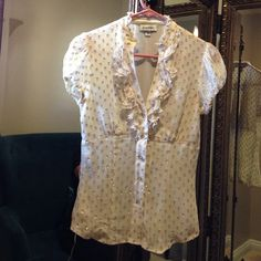 Bebe XS  short sleeve cream blouse w/ gold This has gold flower buttons & sparkly polka dotts. Fitted w/ ruffles around collar & on v neck bust. Super flattering! * under arms have very slight staining , shown in pic * bebe Tops Blouses