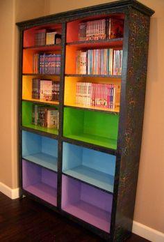 Rainbow coloured bookshelves.