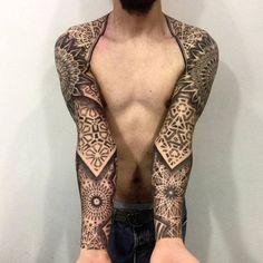 Tatuaje coincidente con patrones geométricos que cubre ambos brazos.
