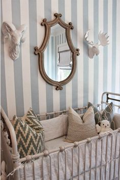 The playful stripe on the wall is lovely combined with the unique mirror and metal framed crib.