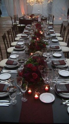 The Christmas wedding featured dark table linens, maroon centerpieces and votive candles to really bring out the dark romance. @myweddingdotcom #MaroonWeddingIdeas