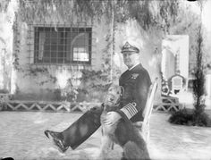 Sir Andrew Cunningham, GCB, DSO, C-in-C, Mediterranean Fleet, wearing his new rank of Admiral of the Fleet, photographed with his Airedale terrier 'Oliver' in the grounds of his villa. c. February 1943 Algiers