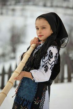 Romanian folk tradition - girl in traditional costume playing the musical instrument bucium