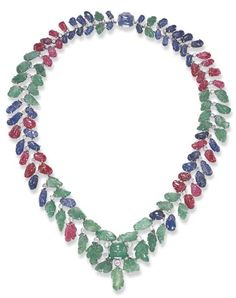 AN IMPRESSIVE ART DECO MULTI-GEM NECKLACE. Of flexible design, the tapering carved sapphire, ruby and emerald band, suspending a similarly-set fringe, enhanced by old European-cut diamond collet, to the central cabochon emerald and sapphire clasp, mounted in white gold, circa 1930, 17 1/8 ins.