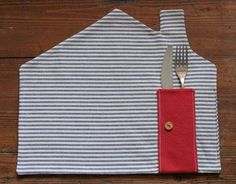 DIY - blue and white stripe fabric house shape   placemat with pitched roof and chimney, red pocket added with button doorknob to hold silverware, cute for home use, housewarming gift, wedding shower, gift for child - looks super easy!  Stripe or red napkin would be cute addition.