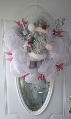 A white deco mesh wreath with a Winter white/gray Santa finished off with cut red ribbons.