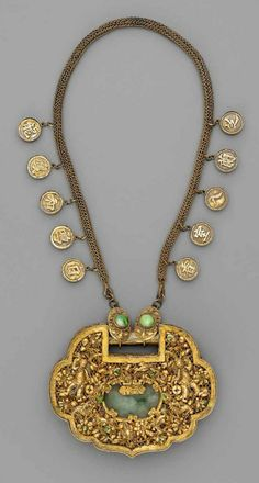 A gilt brass and silver necklace with a large pendant displaying the figures of Hehe Erxian, Buddhist lion-dogs, birds and flowers, the details inset with jade and tiny corals. The chain with round pendants displaying flower sprays and Chinese characters. | Around 1900