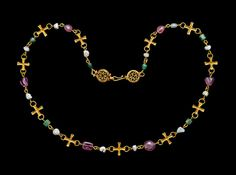 Gold chain, comprising eleven gold crosses strung with links of pearls with six pink tourmaline beads alternating with six green chalcedony beads terminating in openwork discs with hook fastening.  Crosses: Byzantine, circa 600 AD  Pearls and some beads: modern