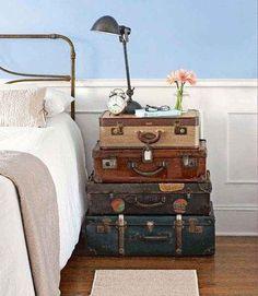 Empilhar uma coleção de malas de viagem velhas para criar uma mesa de cabeceira improvisada.