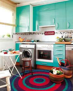 love those aqua cabinets. this kitchen has a somewhat retro kind of look.