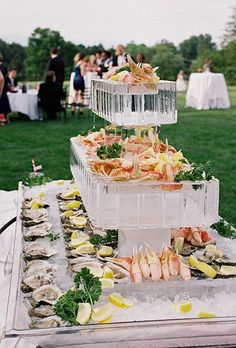 An ice sculpture raw bar featuring tiers of fresh crab legs and oysters.