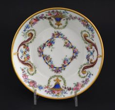 SEVRES c.1789 An 18th Century Sevres Porcelain Saucer. Painted and Gilded with Urns Issuing with Garlands of Garden Flowers and Laurel leaf Swags. The Base Marked with an Interlaced LL for the Sevres Factory and the Sevres Factory Date Code `LL` for 1789. The Painters Mark `P` with a Comma or Small Axe is that of Jean-Jacques Pierre. The Gilders Mark `HP` is for Henry-Martin Prevost Who Worked at Sevres from 1757-1797. R and G McPherson dealers in antique Chinese porcelain