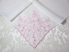 This vintage handkerchief is embellished with the finest hand embroidery of satin stitching, shadow work and rondells in pink floss. It was made by