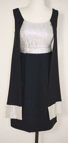 MOD 1960's Black Crepe Vintage Cocktail Dress with a fitted Silver Tinsel Bodice and Babydoll silhouette. Scarf-like Drapes come off the shoulders and hang in front, both are hemmed in the same silver tinsel found on the bodice.