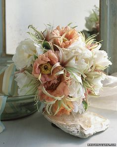 White-and-Peach Bouquet    Cybister amaryllis burst from a cluster of abundant tree peonies the lustrous color of seashells.
