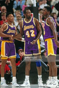 Byron Scott #4, James Worthy #42 and A.C. Green #45 of the Los Angeles Lakers stand against the Portland Trailblazers at the Veterans Memorial Coliseum circa 1993 in Portland, Oregon.