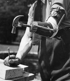 Captain Maxwell uses his artificial arm to hammer in a nail. The arm was supplied by the Ministry of Pensions for service and civilian war casualties, July 1942