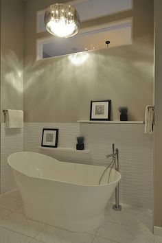 Supply and installation of textured wavy tile on tub surround. Tile by: Ames - White Wavy Gloss 12x24