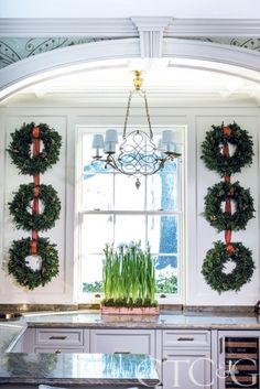 Holiday wreaths flank an antique French chandelier in a kitchen decorated for Christmas. #paperwhites