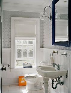"One of the ""MONTAUK BEACH HOUSE"" bathrooms has wainscoting on the walls, a silver grey wallpaper with a circle pattern, a porcelain washstand and a bright orange wastebasket just for fun! I'm kinda liking that funky little light too."