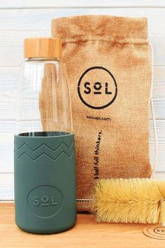 The deep sea green SoL bottle, a beautifully designed glass water bottle with a BPA free silicone sl Eco Friendly Cleaning Products, Eco Products, Kitchen Products, Food Storage Boxes, Drinking Fountain, Stainless Steel Types, Glass Water Bottle, Outfit Trends, Organic Beauty