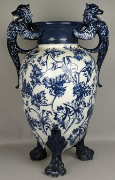 A large earthenware floor urn, possibly Minton, 19th century, of tapering ovoid form and on three lion paw feet with two griffon handles, the body florally decorated in blue and white.