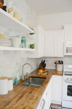 Countertop-to-ceiling marble tile with open shelving and butcher block countertops