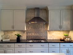 Black and White kitchen, viking appliances, gold glass and stainless steel backsplash, black galaxy granite, white quartz by LG, counter top gas range and Zephyr hood.