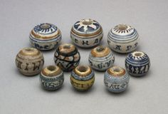 """Bead or spindle-whorl; earthenware covered with a presumed tin glaze and painted in blue and orange: around the middle """"CAteRINA B"""". Italy, 16th century.:"""