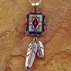 Handmade Sterling Silver pendant from our Santa Fe Inlay Collection. This pendant was designed and made by Navajo artisan Bernyse Chavez of New Mexico. Stones included are Turquoise, Lapis, and Orange & Red Spiny Oyster shell. Each dangling feather also has a Lapis stone at the ends. Bale is large enough for most chains or even a strand of beads.