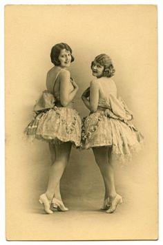 Ретро фотка танцовщиц кордебалета. Позирующие вполоборота девушки одеты одинаково - в балетные пачки с большими бантами за спиной, на ногах - изящные танцевальные туфельки.