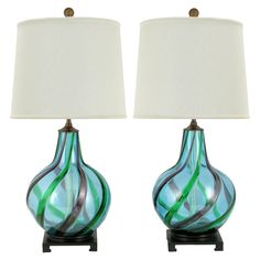 Circa 1950s  Italian art glass at it finest, this pair of Murano glass gourd form table lamps are hand blown in an exquisite shade of aqua blue with emerald and amethyst striped swirls. The base is a carved and ebonized plinth and the pierced brass ball finial finishes.