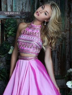 Step out in vivaciously vibrant style in the Sherri Hill 50310 two-piece prom dress. This full-length ensemble shimmers in satin. The halter neck crop top has a semi-open back and is stunningly embellished with a brightly beaded design. A beaded waistband adorns the long full skirt as it cascades over a filmy sheer underskirt, creating a voluminous A-line silhouette.