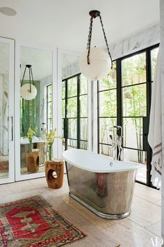 A JF Chen globe lantern hangs above a Waterworks tub with a burnished-nickel finish in Kayne's bathroom | archdigest.com