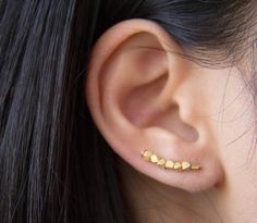 Put these on and feel like an instant badass. This earring is dotted with delicate matte gold beveled beads, then curved slightly for the optimal look